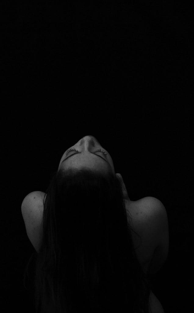 La photo sur fond noir, une femme de dos la tête en arrière regarde le plafond. Elle a de longs cheveux bruns, qui semblent glisser le long de son dos nu. Ses épaules sont dénudées aussi. Cette image représente l'état de noirceur et de solitude dans lequel la maladie peut nous plonger.